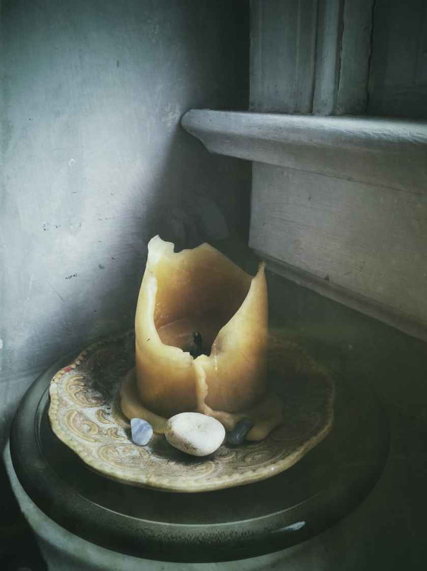 beige candle on beige saucer plate beside polished pebbles near window